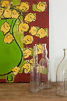 An oil on canvas by Sirianni beside a collection of empty glass bottles decorates one of the hotel bedrooms
