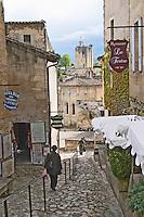 person walking on a cobble stone street saint emilion bordeaux france