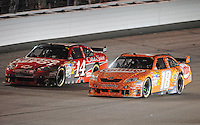 May 2, 2009; Richmond, VA, USA; NASCAR Sprint Cup Series driver Kyle Busch (18) races alongside Tony Stewart (14) during the Russ Friedman 400 at the Richmond International Raceway. Mandatory Credit: Mark J. Rebilas-