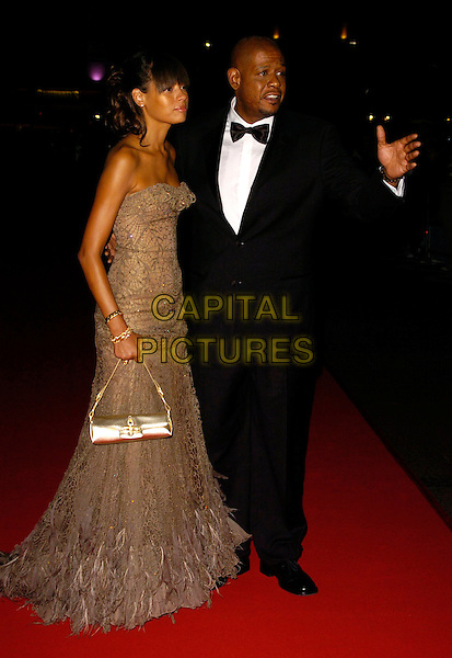 "KEISHA WHITAKER & FOREST WHITAKER.The Times BFI London Film Festival opening night with the screening of ""The Last King Of Scotland"" at the Odeon Leicester Square, London, UK..October 18th, 2006.Ref: CAN.full length black tuxedo brown gold strapless dress feathers husband wife married.www.capitalpictures.com.sales@capitalpictures.com.©Can Nguyen/Capital Pictures"