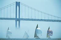 Sailboats race from through the fog