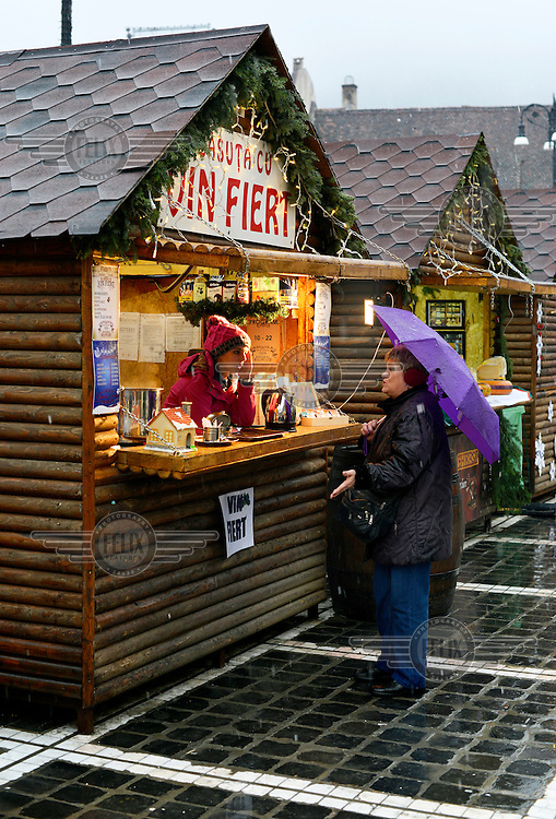 A stall holder selling fortified wine chats with a local resident in the main square of Brasov which is holding the annual Christmas Market.
