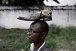 "KINSHASA, DEMOCRATIC REPUBLIC OF CONGO - FEBRUARY 10: A young Sapeur wears a shoe on his head as he parades and shows his designer label clothes while paying their respect to Stervos Nyarcos, the founder of the kitendi religion, which means clothing in local language Lingala. Nyarcos was known as the leader of the Sape movement, at Gombe cemetery on February 10, 2012 in Kinshasa, DRC. The word Sapeur comes from SAPE, a French acronym for Société des Ambianceurs et Persons Élégants or Society of Revellers and Elegant People and it also means, to dress with elegance and style"". Most of the young Sapeurs are unemployed, poor and live in harsh conditions in Kinshasa,  a city of about 10 million people. For many of them being a Sapeur means they can escape their daily struggles and dress like fashionable Europeans. Many hustle to build up their expensive collections. Most Sapeurs could never afford to visit Paris, and usually relatives send or bring clothes back to Kinshasa. (Photo by Per-Anders Pettersson)"
