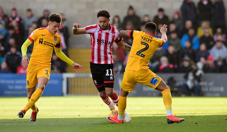 Lincoln City's Bruno Andrade vies for possession with Northampton Town's Shaun McWilliams, left, and Northampton Town's Shay Facey<br /> <br /> Photographer Chris Vaughan/CameraSport<br /> <br /> The EFL Sky Bet League Two - Lincoln City v Northampton Town - Saturday 9th February 2019 - Sincil Bank - Lincoln<br /> <br /> World Copyright &copy; 2019 CameraSport. All rights reserved. 43 Linden Ave. Countesthorpe. Leicester. England. LE8 5PG - Tel: +44 (0) 116 277 4147 - admin@camerasport.com - www.camerasport.com