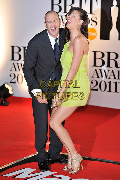 JOHNNY VAUGHAN & LISA SNOWDON  .The BRIT Awards 2011 at the O2 Arena, London, England..February 15th, 2011.brits full length black suit green neon fluorescent one shoulder dress side profile mouth open laughing smiling funny gold shoes clutch bag.CAP/MAR.© Martin Harris/Capital Pictures.