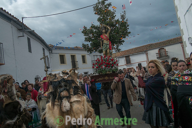 "Carantoñas precede the statue of Saint Sebastian  during the Carantoñas festival, in Acehúche near Cáceres, on January 21, 2015. The ""Carantoñas"", monster-animal characters mixing paganism with Christianity, search for Saint Sebastian in the streets of the village of Acehúche, southwestern Estremadure province, dressed in patchwork sheep, cow, rabbit and goatskins under painted masks. Arriving eventually at the village church, a procession takes place with the statue of the patron saint. Until recently, Spain's neighbors, the Berbers of Morocco, preserved a version of the same ritual in their animal-hided winter ""goblin,"" Bou Inania.  © Pedro ARMESTRE"