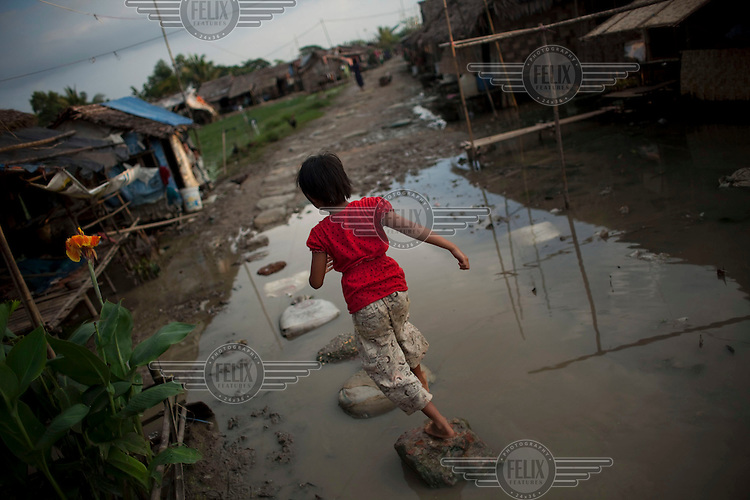 A child walks across stepping-stones in a puddle of stagnant water in the Hlaing Thaya slum district of Yangon.