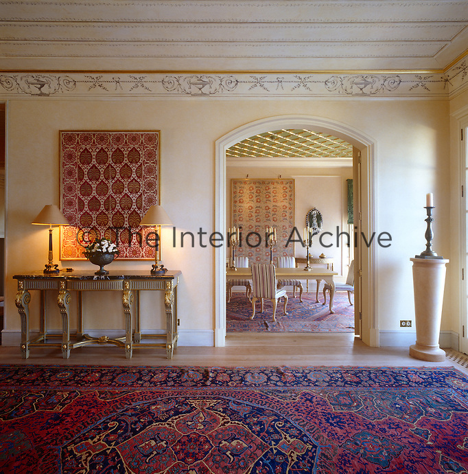 A view through from the entrance hall to the dining room, which is also furnished with richly patterned Turkish rugs and wall hangings