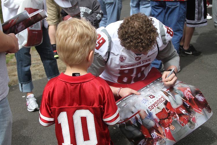 Travis Long signs autographs prior to the culmination of the first spring practice under new head coach Mike Leach at the annual Crimson and Gray game at Joe Albi stadium in Spokane, Washington, on Saturday, April 21, 2012.