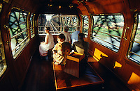Passengers enjoying sunrise in the observation car of the Eastern & Oriental Express.
