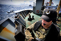 Dutch battleship Hr Ms Evertsen can be seen in the background as a member of the Dutch Special Forces stands guard aboard the Fade I cargo ship, a WFP (World Food Program) vessel delivering 5,000 tonnes of food aid to Somalia. Many aid ships have been hijacked by pirates in these waters, and the Dutch Navy monitor the vessels to try and prevent further attacks.