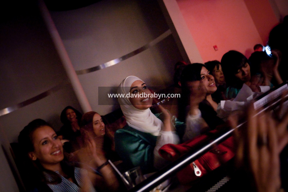 Audience members watch an act during the 6th Annual NY Arab-American Comedy Festival in New York, USA, watch the on-going act on a screen from the changing room, 13 May 2009.