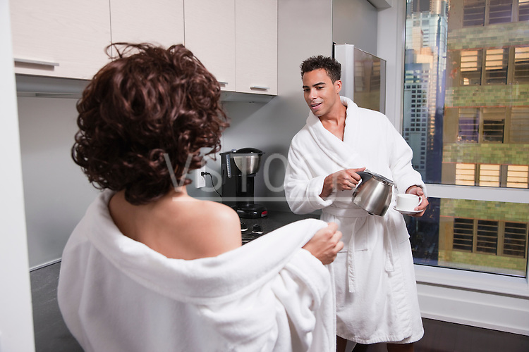 USA, New York City, woman undressing in front of man in kitchen