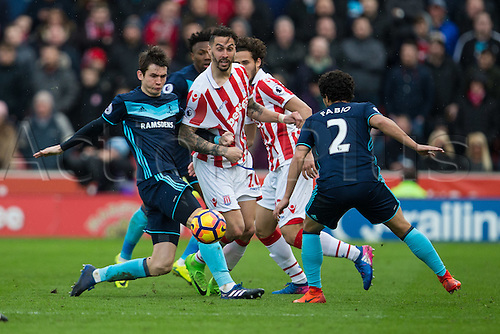 March 4th 2017,  bet365 Stadium, Stoke, England; EPL Premier League football, Stoke City versus Middlesbrough; Stoke's Geoff Cameron and Middlesbrough's Fabio and Marten de Roon fight over a loose ball