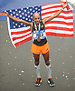 Meb Keflezighi poses for pictures carrying an American flag after finishing the TCS New York City Marathon on Sunday, Nov. 5, 2017.