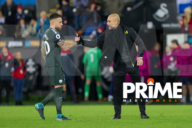 Manchester City manager Pep Guardiola congratulates Nicolas Otamendi of Manchester City at full time of the EPL - Premier League match between Swansea City and Manchester City at the Liberty Stadium, Swansea, Wales on 13 December 2017. Photo by Mark  Hawkins / PRiME Media Images.