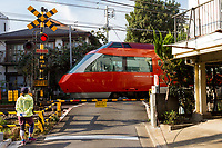A joggers waits at a level crossing while an Odakyu 70000 series GSE Romance Car passes.  Sangubashi, shinjuku, Tokyo, Japan. Wednesday November 21st 2018