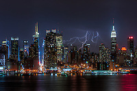 Lightning bolts illuminate the night sky behind the skyline of New York City during a summer thunderstorm on Sunday, July 15, 2012.