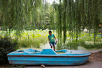 A boy looks at a pedal boat out of water in Changle Park in Xian, Shaanxi Province, China.