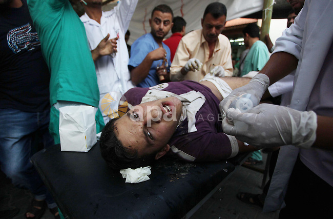 Palestinian medics treat a man, whom medics said was wounded in an Israeli air strike, at a hospital in Rafah in the southern Gaza Strip August 4, 2014. A brief Israeli truce to allow aid to reach Palestinians ended on Monday amid accusations of strikes by both sides, while Jerusalem was rocked by two attacks that appeared to be a backlash against the war in Gaza. Gaza officials say 1,831 Palestinians, most of them civilians, have been killed and more than a quarter of the impoverished enclave's 1.8 million residents displaced. As many as 3,000 Palestinian homes have been destroyed or damaged. Israel has lost 64 soldiers in combat and three civilians to Palestinian cross-border rocket and mortar fire that has emptied many of its southern villages. Iron Dome interceptors, air raid sirens and public shelters have helped stem Israeli casualties. Photo by Ashraf Amra