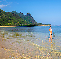 A snorkeler holds her fins in the clear shallow waters of Tunnels Beach, Kaua'i; other snorkelers explore deeper waters in the distance. (NOTE: Snorkeler in foreground is model released; the others are not.)