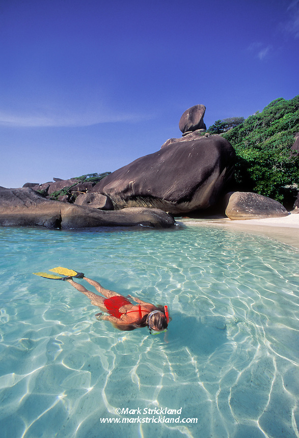 A snorkeler explores sunlit shallows at Ko Similan, Similan Islands Marine National Park, Thailand