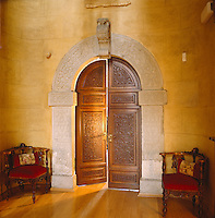 The arched doorway to the Music Room dates back to the part of the castle which was built in the 17th century and is flanked by a pair of corner armchairs