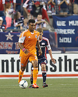 Houston Dynamo midfielder Giles Barnes (23) passes the ball as New England Revolution midfielder Scott Caldwell (6) defends. In a Major League Soccer (MLS) match, Houston Dynamo (orange) defeated the New England Revolution (blue), 2-1, at Gillette Stadium on July 13, 2013.