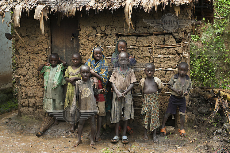 A group of children stand outside a mudbrick hut.
