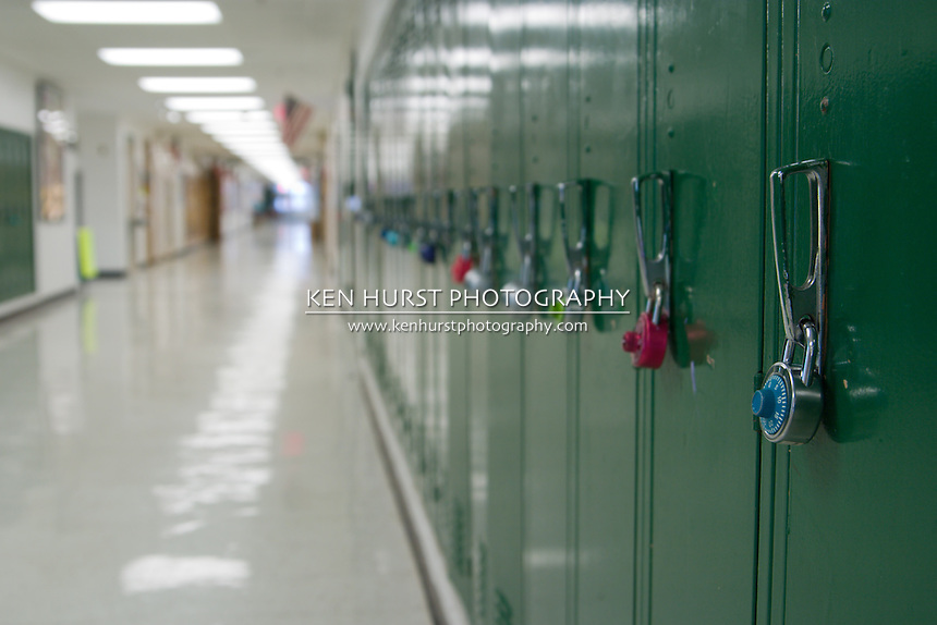 Closeup view of a lock on a school locker with row of lockers and and empty school hallway in background out of focus from depth of field.