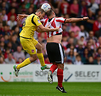 Morecambe's Dean Winnard vies for possession with Lincoln City's Matt Rhead<br /> <br /> Photographer Chris Vaughan/CameraSport<br /> <br /> The EFL Sky Bet League Two - Lincoln City v Morecambe - Saturday August 12th 2017 - Sincil Bank - Lincoln<br /> <br /> World Copyright &copy; 2017 CameraSport. All rights reserved. 43 Linden Ave. Countesthorpe. Leicester. England. LE8 5PG - Tel: +44 (0) 116 277 4147 - admin@camerasport.com - www.camerasport.com