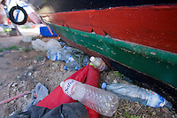 Cimitero delle barche...I barconi che trasportano i profughi vengono depositati in tre punti dell isola in attesa di essere smaltiti. ..Bottiglie d acqua e oggetti vari sparsi vicino alle barche depositate nei pressi del porto...Lampedusa 05 Marzo 2011...Photo Serena Cremaschi Insidefoto..........