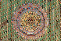 Painted decorative ceiling of the Prayer hall of the Helveti Tekke or Teqe e Helvetive, a Bektashi Sufi shrine of the Helveti sect built in the 15th century and rebuilt by Ahmet Kurt Pasha in 1782, with mihrab on the far wall, in Berat, South-Central Albania, capital of the District of Berat and the County of Berat. The ceiling is decorated in the Baroque style adopted by Islamic art and 14 carat gold has been used. The tekke is composed of a square prayer hall, an external portico (with columns from Appolonia) and a room which housed the mausoleum of Ahmet Kurt Pasha and his son. On the inner walls are 8 frescoes of houses, muslim religious buildings and gardens. Picture by Manuel Cohen