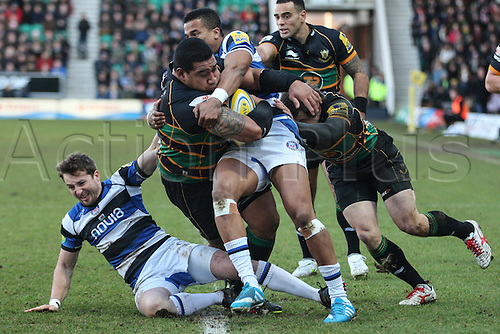 28.12.2013 Northampton, England. Salesi MA'AFU of Northampton Saints is tackled by Martin ROBERTS (left) and Anthony WATSON (right) of Bath during the Aviva Premiership match between Northampton Saints and Bath Rugby at Franklins Gardens.