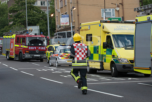 Kingston upon Thames, England. Command Staff fireman running in the road at an incident with fire engines, police car and ambulance.
