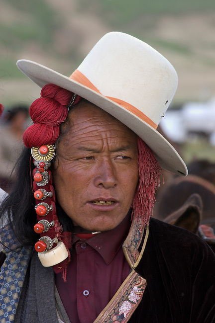 Khampa with jaunty cowboy hat and ivory hair peices at the  Litang Horse Festival  in Kham - Sichuan Province, China, (Tibet)