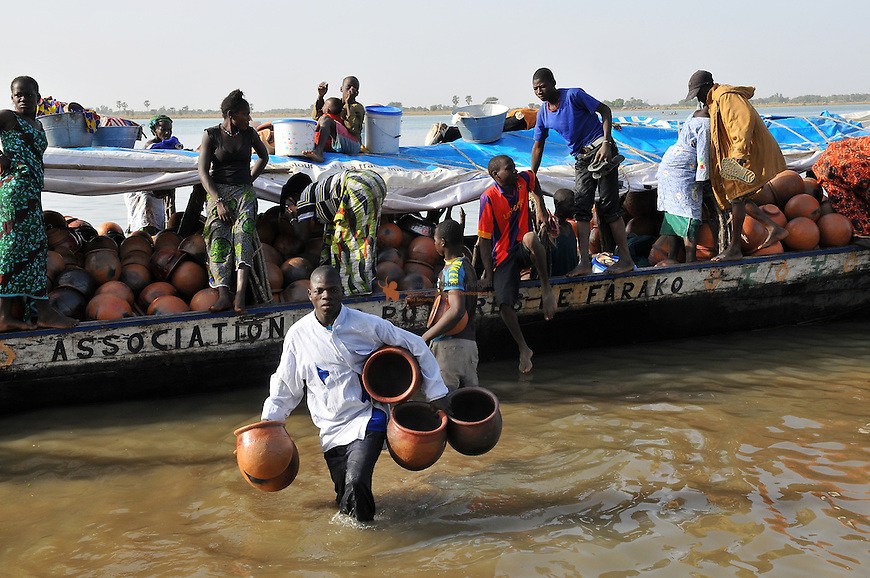 Hand made pottery being unloaded from a traditional boat onto the banks of the Niger river in Mali