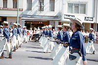 Vintage view of the Edna Cowboys high school marching band in colorful western uniforms of chaps, blue western shirts and western hats and boots marching up Congress Avenue during downtown Austin parade, circa 1960s - Stock Image.