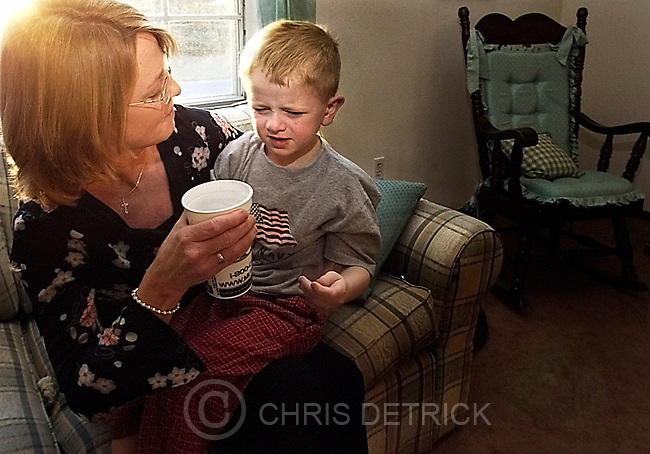 CHRIS DETRICK/Missourian    424-9366.Pam Lanham helps administer a dose of Concerta to her son Grant, 7, Thursday March 11, 2004 in the living room of their Columbia, Mo., home.  Like his older brother Jordan, Grant also suffers from Attention Deficit Hyperactivity Disorder and has been on medication since he was four years old.  Grant began taking Ritilin, which did not work well so now takes Concerta.  The Lanham family feels that with out the perscription drugs, Jordan and Grand would not be able to achieve in school.