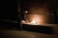 4 April 2012 Beijing, 22h30. A woman is burning replicas of banknotes and funeral papers to honor the remembrance of dead relatives in the last day of Qingming festival.