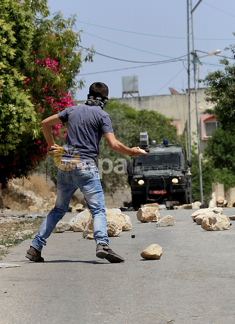 A Palestinian protester uses a slingshot to throw stones towards Israeli security forces during clashes following a demonstration against the expropriation of Palestinian land by Israel, on May 20, 2016 in the village of Kfar Qaddum, near Nablus, in the occupied West Bank. Photo by Nedal Eshtayah