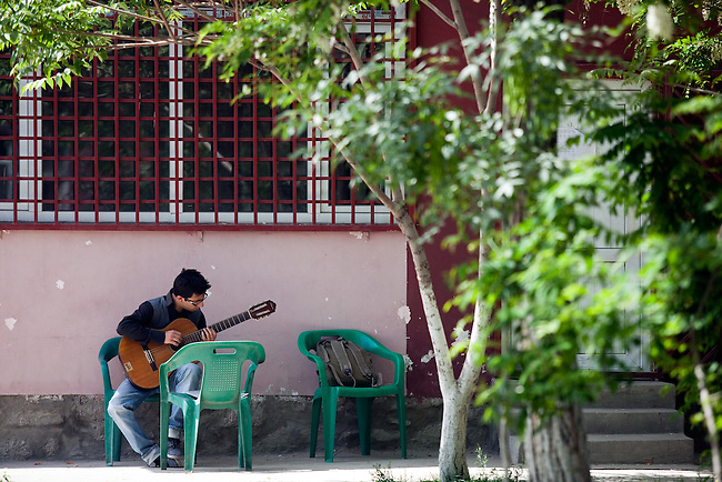 18 May 2012, Kabul Afghanistan:  A guitar student practises in the grounds at the National Institute of Music. Dr Ahmad Nasir Sarmast founded the Afghanistan National Institute of Music in Kabul that takes in students from all walks of Afghan life to educate them in musical studies. The World Bank is supporting this legacy by providing funding for a new concert hall and to gather additional land to expand the premises. Many of the students are orphans who would otherwise have no opportunity or access to the knowledge or instruments that the Institute has gathered. Up to half a dozen ex-patriate music  teachers run classes in music that ranges from traditional Afghan and classical  music to modern rock.  Picture by Graham Crouch/World Bank