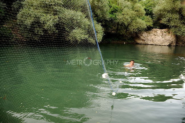 CHUMI GOALEYA, IRAQ: Sewan swims across the river to set his nets.<br /> <br /> Fishermen high in the Kurdish mountains use nets to catch river fish.  <br /> <br /> Photo by Pazhar Muhammed