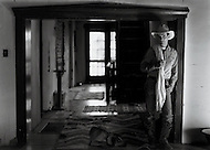 A cowboy stands in his home.