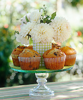 A cake stand with homemade muffins and decorated with a vase of Dahlias