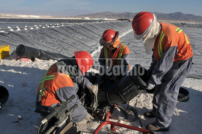 Workers build around the clock a new pond for SQM company in Salar de Atacama, North of Chile.