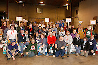 "An army of ""food drop"" volunteers pose for a group photo during a break in thier work.  These volunteers move, sort, weigh, and stack the mushers tens of thousands of pounds of food and gear for the 22 checkpoints.   Iditarod 2009"