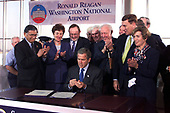 United States President George W. Bush signs the Aviation security bill at Ronald Reagan Washington National Airport in Washington, DC on November 19, 2001.  At left is US Secretary of Transportation Norman Mineta.<br /> Credit: Ron Sachs / CNP