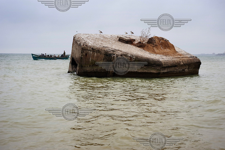 A boat full of fishermen rows past a WWII concrete pillbox half submerged in the waters of the Black Sea.