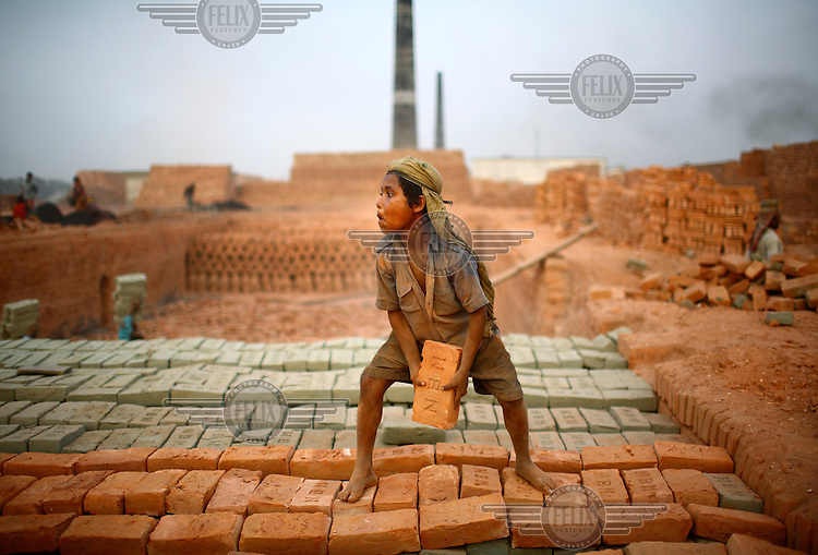A child moves loads of bricks by throwing them along a human chain at a brick making factory in Gazipur. For each thousand bricks they move the labourers are paid the equivalent of about GBP 0.56.